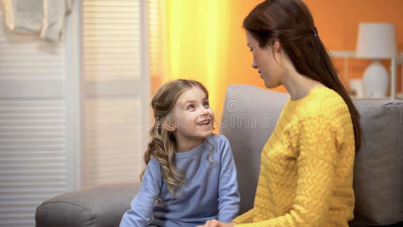 Muchacha alegre que escucha cuidadosamente para mimar a contar la historia divertida, momentos felices fotos de archivo libres de regalías