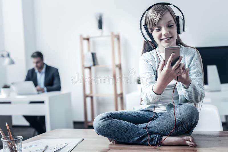 Muchacha alegre que escucha la música mientras que se sienta en la tabla fotografía de archivo