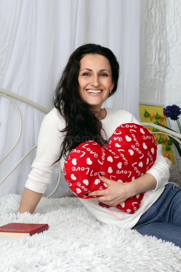 Muchacha alegre y bonita joven que se sienta en la cama, ella sostiene una almohada en forma de corazón estudio imagen de archivo libre de regalías