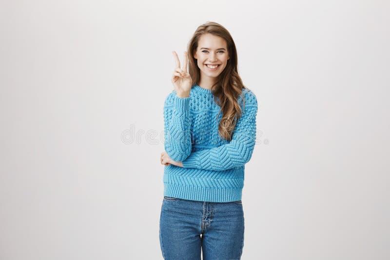 Muchacha alegre y sincera que muestra la victoria o el signo de la paz mientras que cruza la mano y sonríe ampliamente, teniendo  foto de archivo