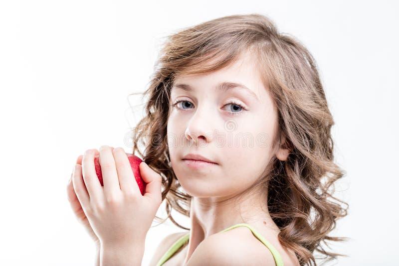 Muchacha alrededor para morder una manzana roja en el fondo blanco imagen de archivo libre de regalías