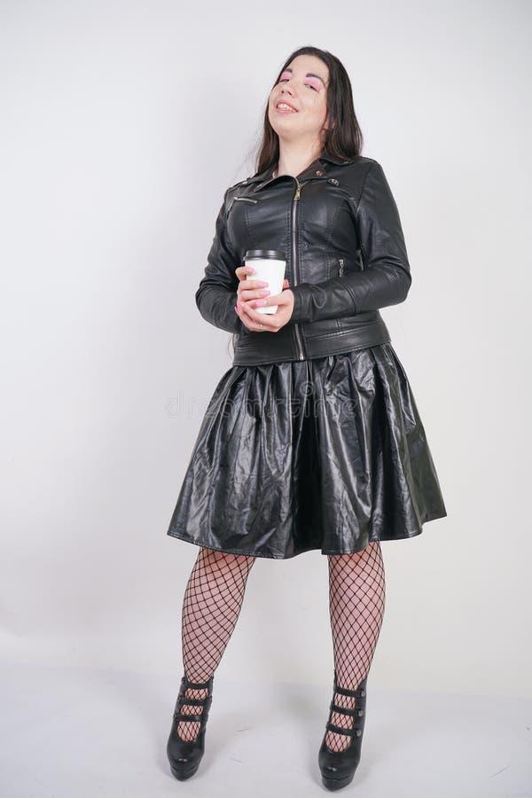 Muchacha alternativa de moda con una taza de caf? de papel en un fondo blanco en el estudio imagen de archivo libre de regalías