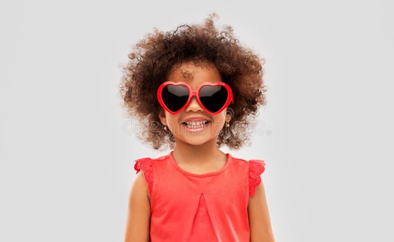 Muchacha ameican africana en gafas de sol en forma de coraz?n imagen de archivo