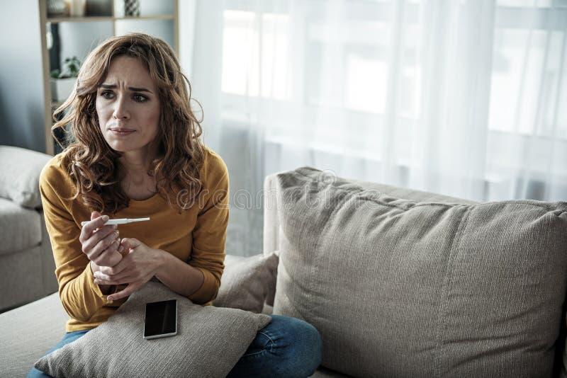 Muchacha ansiosa que sostiene el palillo de la prueba de embarazo imagenes de archivo