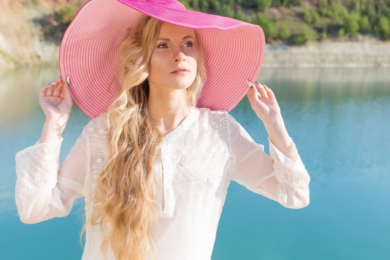 Muchacha apacible dulce hermosa en el vestido blanco en sombrero rosado grande ligero en la orilla del mar azul en el sol de la t fotos de archivo
