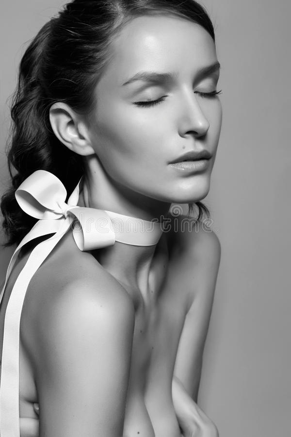 Muchacha apacible hermosa con el arco de seda en el hombro derecho foto de archivo libre de regalías