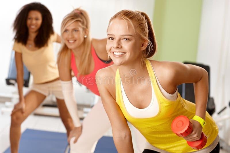 Muchacha apta que ejercita con la sonrisa de las pesas de gimnasia imagen de archivo libre de regalías