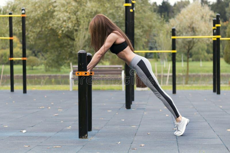 Muchacha apta que hace el ejercicio del tablón al aire libre en el día de verano caliente del parque Concepto de resistencia y de fotografía de archivo