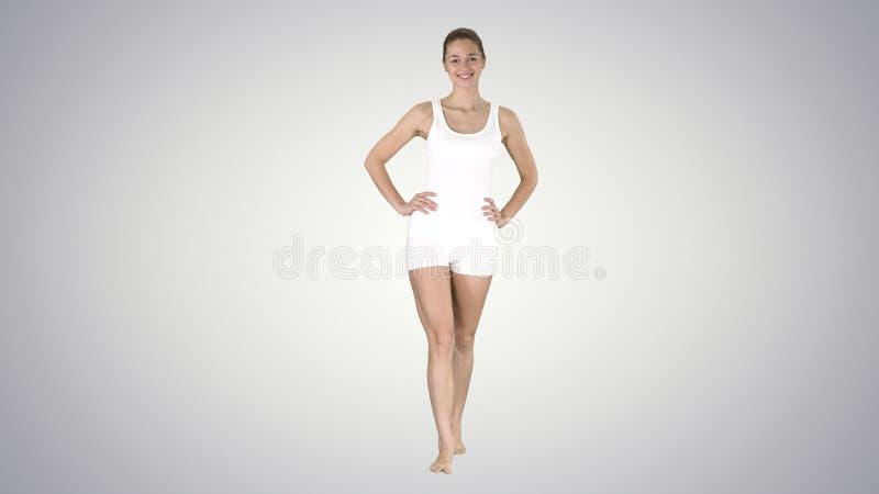 Muchacha apta y deportiva en ropa interior de la pendiente que camina descalzo con las manos en sus caderas en fondo de la pendie fotografía de archivo