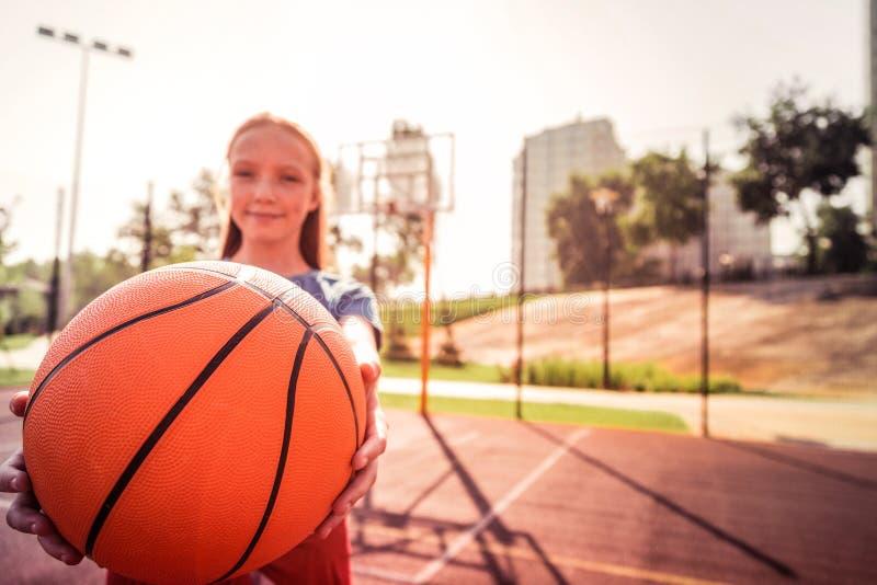 Muchacha apuesta sonriente que sostiene firmemente la bola brillante del baloncesto imágenes de archivo libres de regalías