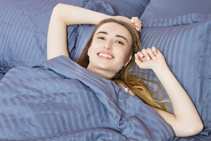 Muchacha ascendente cercana de la sonrisa que despierta en la cama por la ma?ana foto de archivo libre de regalías
