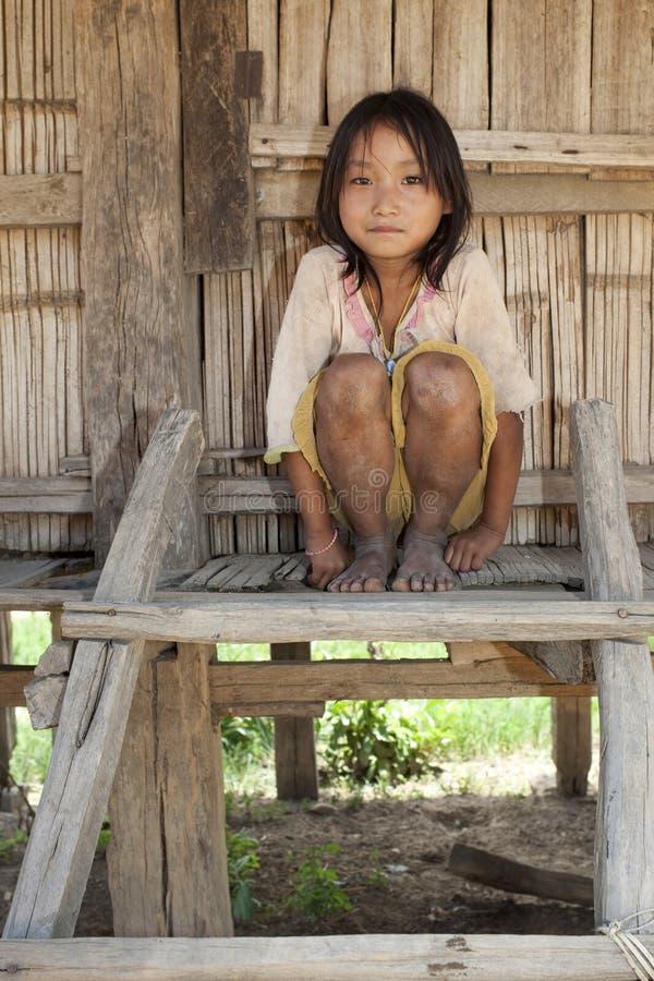 Muchacha asiática Akha antes de la casa de la madera, Laos imagenes de archivo