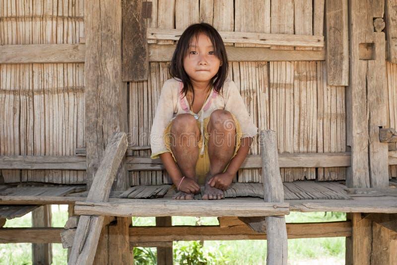 Muchacha asiática Akha antes de la casa de la madera, Laos imagen de archivo libre de regalías