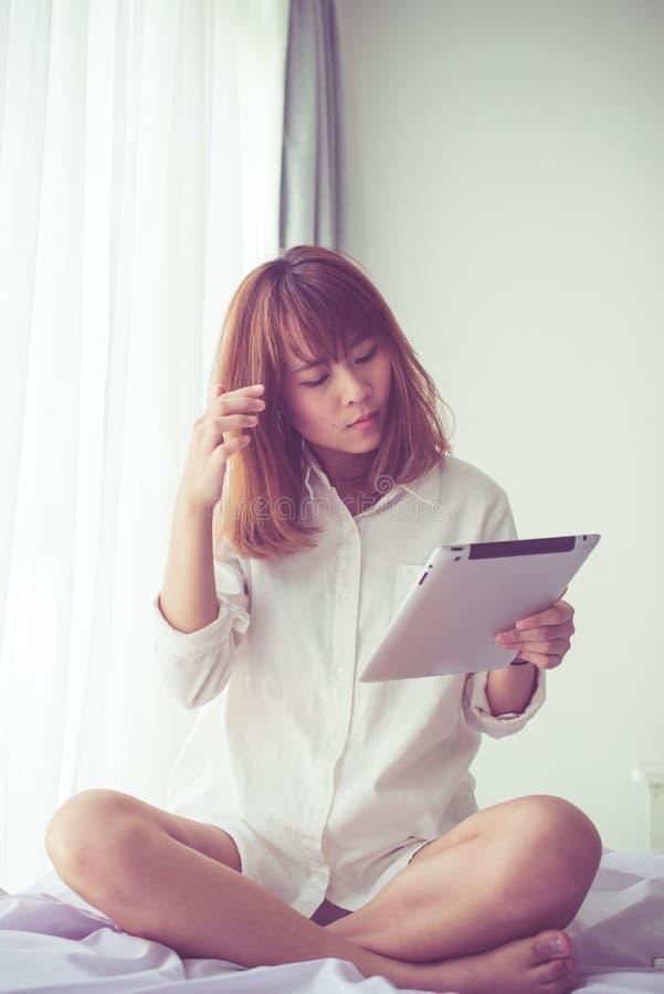 Muchacha asiática asombrosamente del adolescente que usa la tableta fotos de archivo
