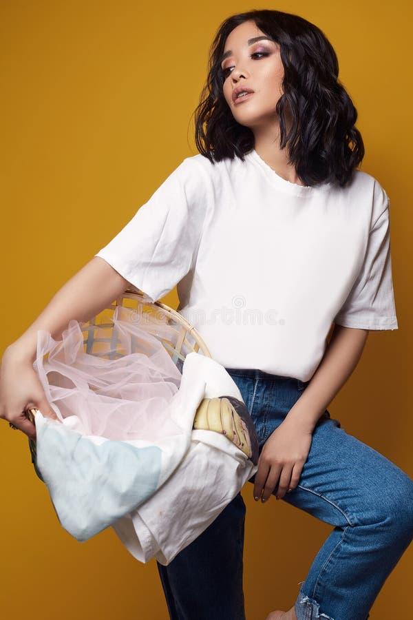 Muchacha asiática atractiva elegante en vaqueros y camiseta blanca en fondo brillante imagen de archivo libre de regalías