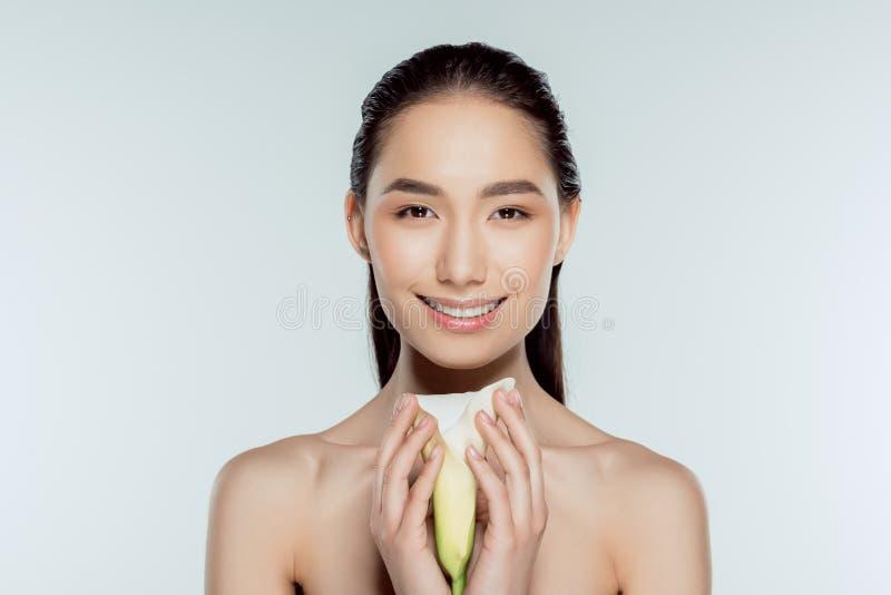 muchacha asiática atractiva feliz con la flor de la cala imagenes de archivo