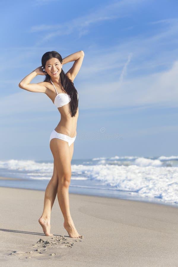 Muchacha asiática china de la mujer joven en bikiní en la playa fotos de archivo