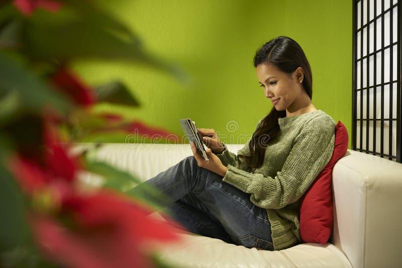Muchacha asiática con la almohadilla táctil que se relaja en el sofá en casa imágenes de archivo libres de regalías