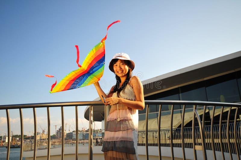 Muchacha asiática con la cometa bajo el sol imagen de archivo libre de regalías