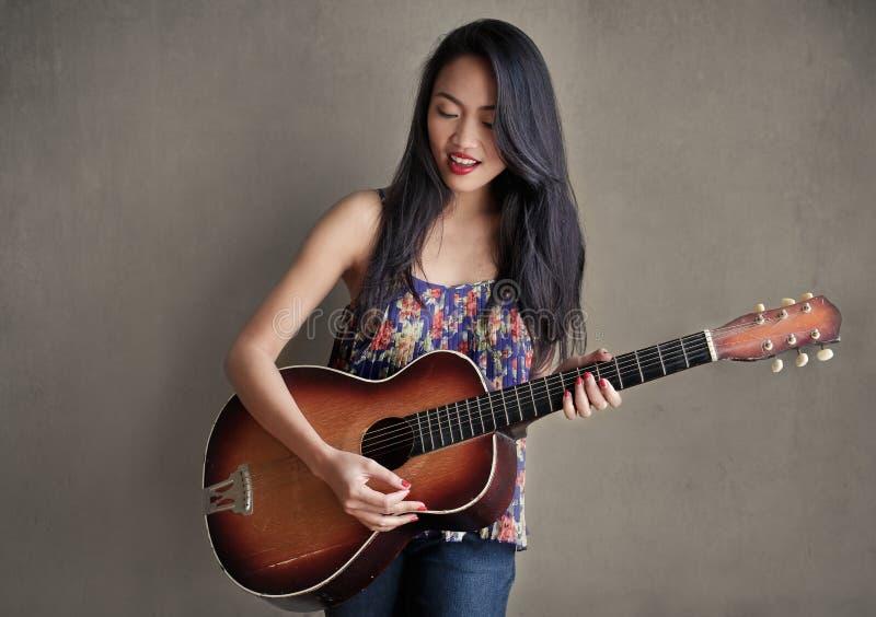 Muchacha asiática con la guitarra imagenes de archivo
