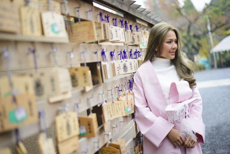 Muchacha asiática con la muestra que desea de madera japonesa en la pared en el templo fotos de archivo