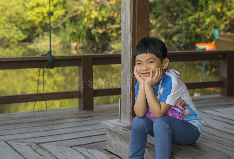 Muchacha asiática con la sonrisa grande que se sienta en el piso de madera imagenes de archivo