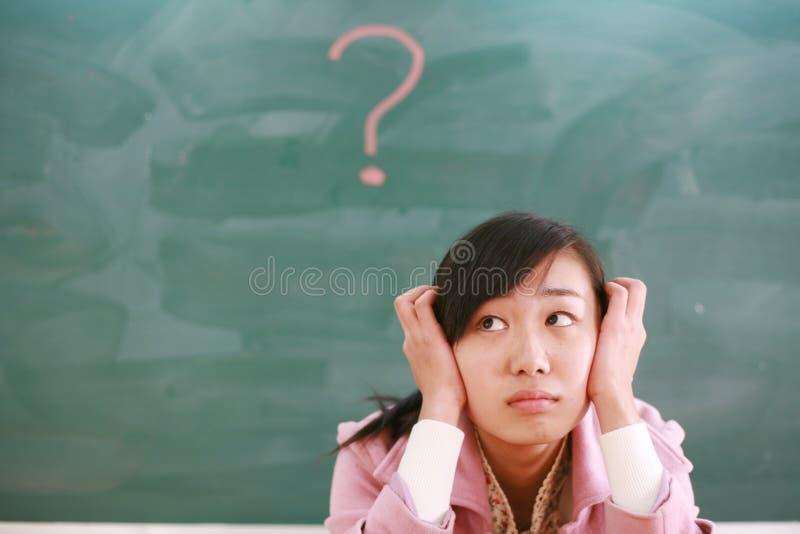 Muchacha asiática con un signo de interrogación rojo imagen de archivo