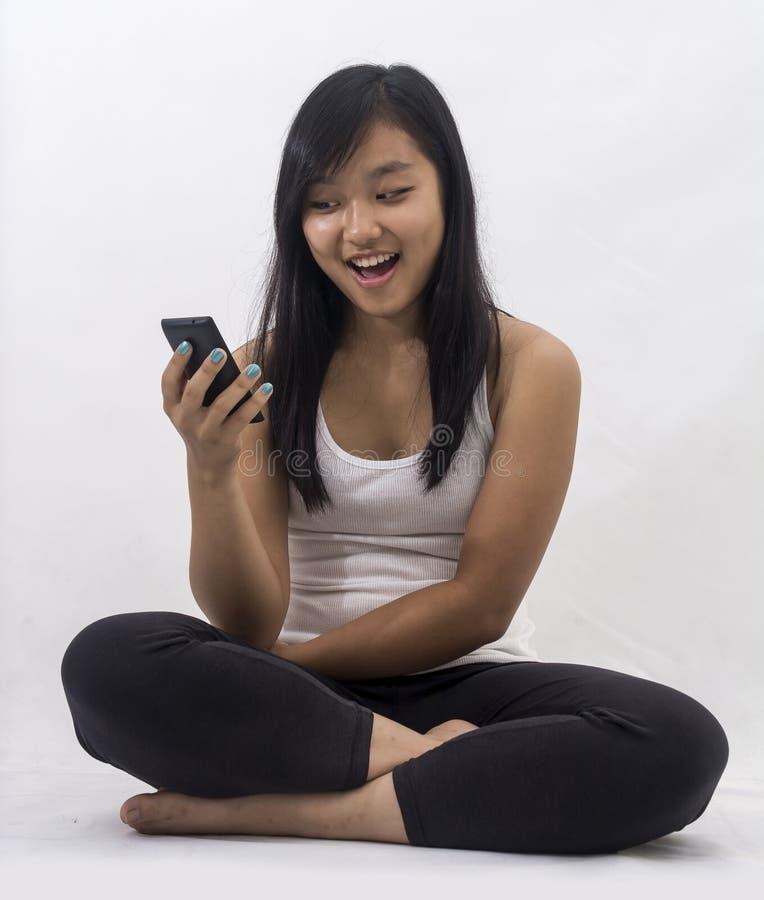 Muchacha asiática con un teléfono elegante imagenes de archivo