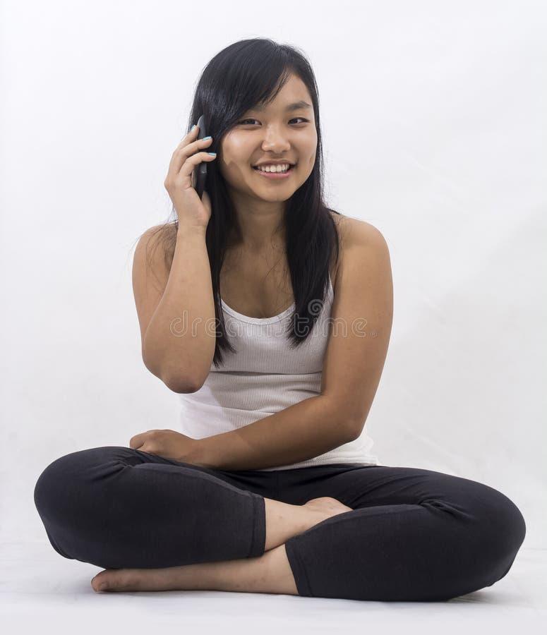 Muchacha asiática con un teléfono elegante imagen de archivo libre de regalías