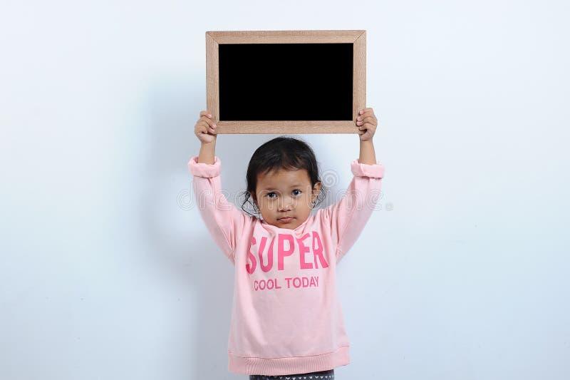 Muchacha asi?tica cortada que sostiene la pizarra o la pizarra en blanco Usted puede mandarle un SMS de nuevo a escuela fotografía de archivo libre de regalías
