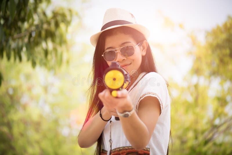 Muchacha asiática de la belleza feliz joven con la camisa del verano del arma de agua que lleva en el festival de Songkran - fes foto de archivo libre de regalías