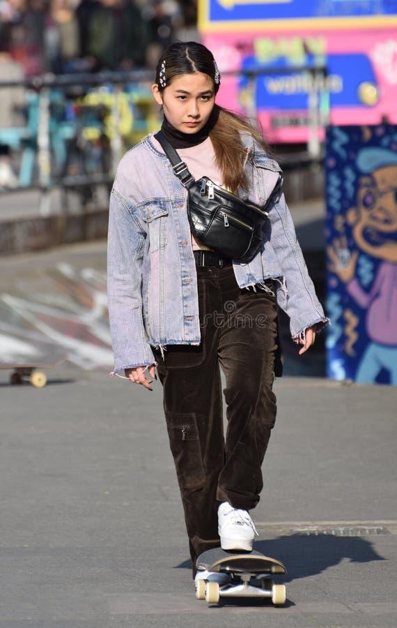 Muchacha asiática de los jóvenes de moda que anda en monopatín Londres, Reino Unido En marzo de 2019 fotografía de archivo libre de regalías