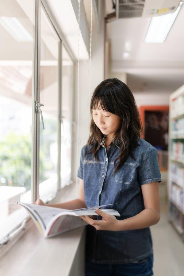 Muchacha asiática del estudiante en sitio de la biblioteca foto de archivo