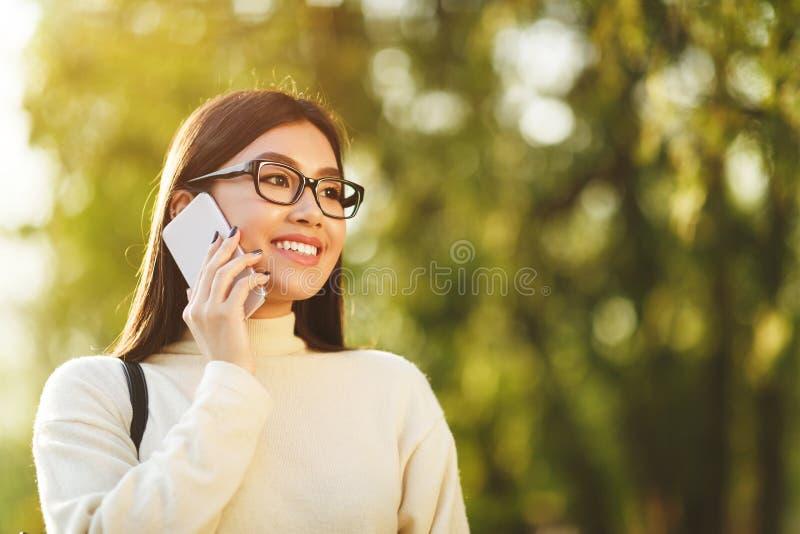 Muchacha asiática del estudiante que habla en el teléfono en parque de la ciudad fotos de archivo