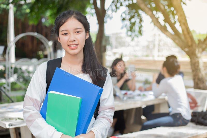 Muchacha asiática del estudiante que sostiene el libro en campus y escuela imagen de archivo