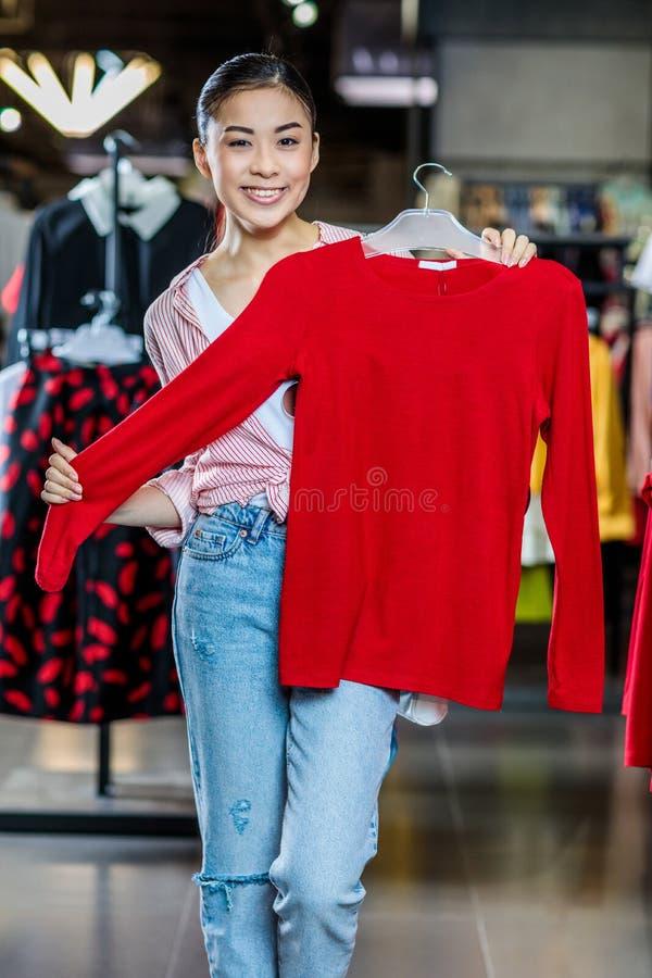 Muchacha asiática del inconformista que elige la ropa en alameda de compras fotografía de archivo libre de regalías