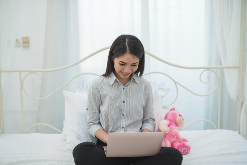 Muchacha asiática del negocio feliz y sonrisa mientras que trabaja con un ordenador portátil foto de archivo