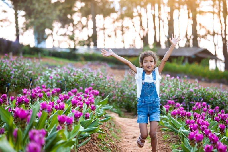 Muchacha asiática del niño aumentar sus brazos y correr en el jardín de flores con frescura y felicidad imagenes de archivo