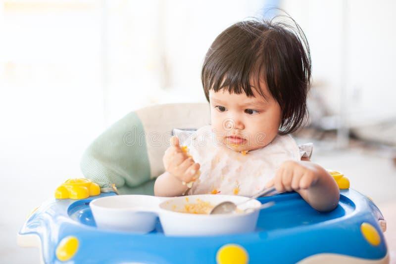 Muchacha asiática del niño del bebé lindo que come la comida sana sola foto de archivo libre de regalías
