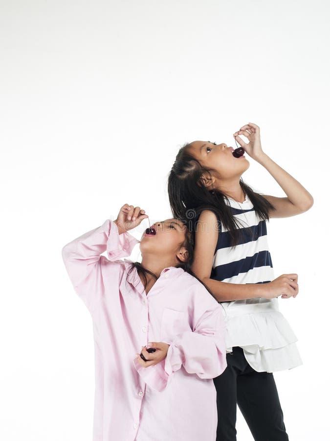 Muchacha asiática del niño de dos hermanas aislada en el fondo blanco foto de archivo