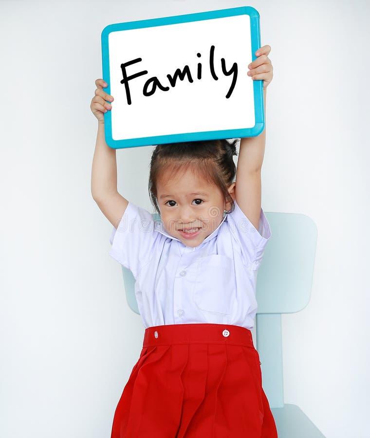 Muchacha asiática del niño en whiteboard de la tenencia del uniforme escolar con el texto 'familia 'en el fondo blanco fotos de archivo libres de regalías