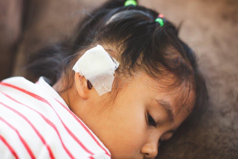 Muchacha asiática del niño herida en el oído El oído del niño con el vendaje después de que ella haya sido accidente imágenes de archivo libres de regalías