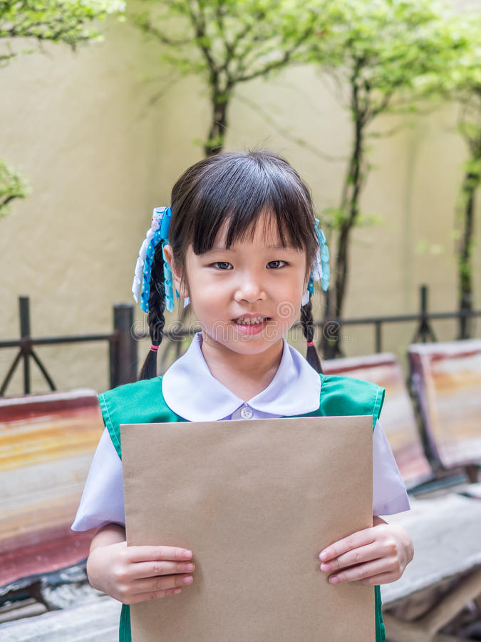 Muchacha asiática del niño que sostiene un sobre marrón fotos de archivo