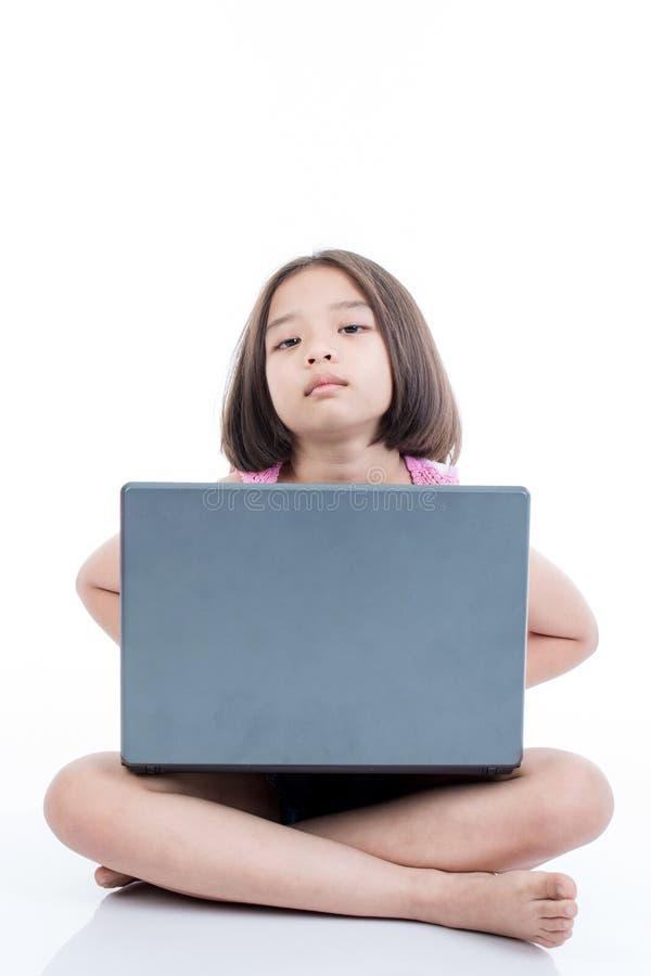 Muchacha asiática del niño que usa el ordenador portátil y el taladro imagenes de archivo
