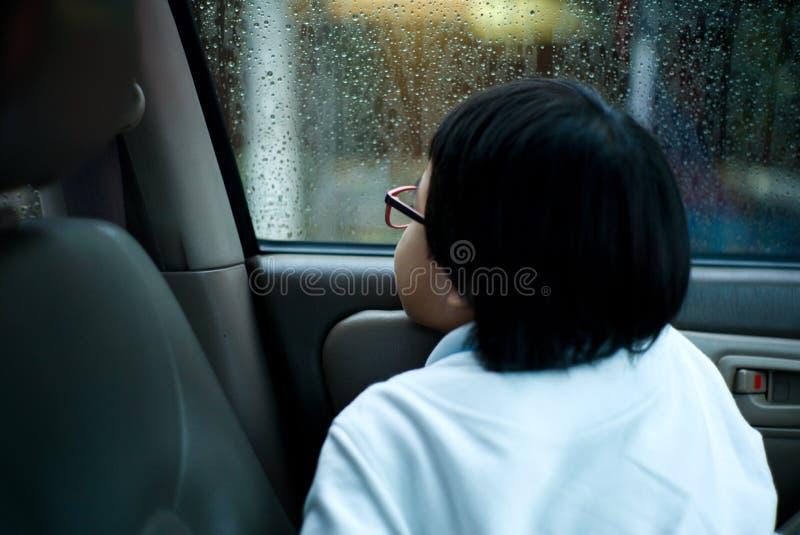 Muchacha asiática del retrato que se sienta en coche y que mira fuera de la ventana que mira la lluvia imagenes de archivo