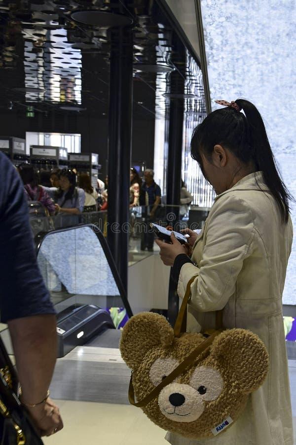 Muchacha asiática elegante joven hermosa con un teléfono celular fotografía de archivo libre de regalías
