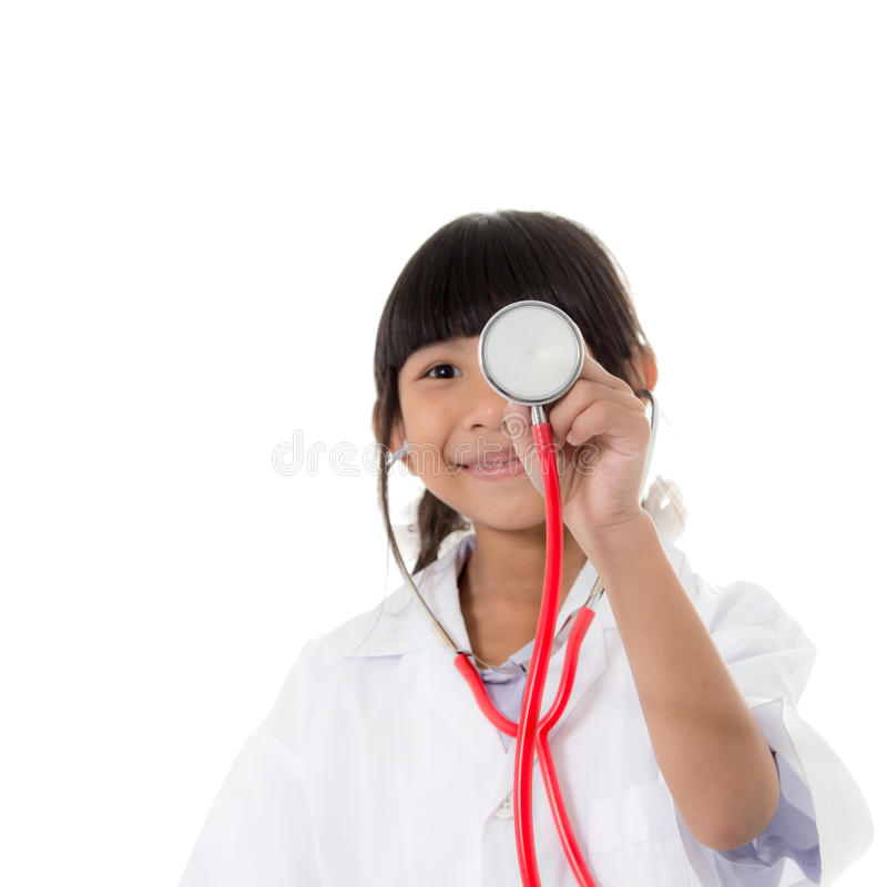 Muchacha asiática en la capa del doctor y el estetoscopio el sostenerse fotos de archivo