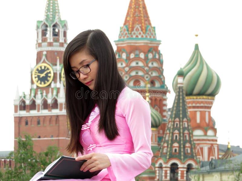 Muchacha asiática en lentes que lee un libro en Moscú imagen de archivo
