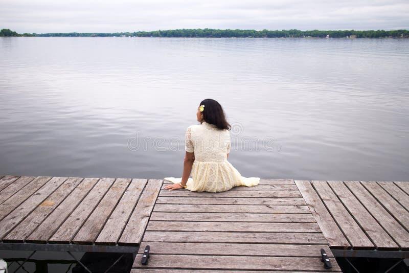 Muchacha asiática en un vestido blanco que se sienta en un muelle imagen de archivo