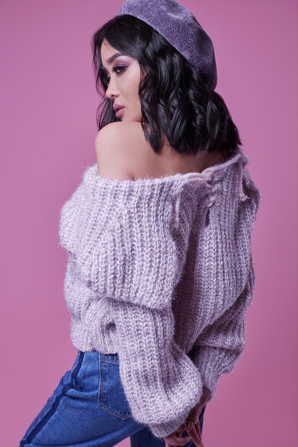 Muchacha asiática encantadora hermosa en suéter púrpura en fondo rosado brillante fotografía de archivo libre de regalías